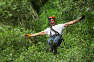 Man zip lining through the trees at Empower Adventures