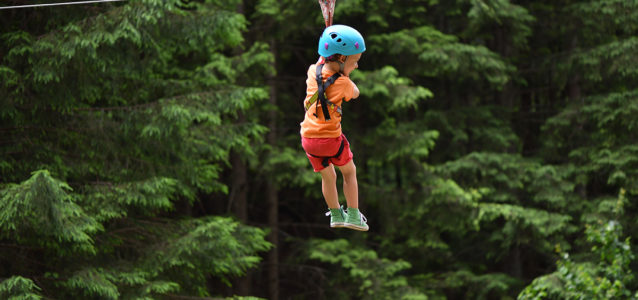Little girl on a zip line adventure in the trees