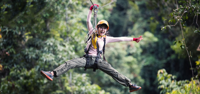 Young woman having fun on a zipline adventure tour